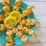 Seasoned shrimp skewers garnished with lemon slices on a blue plate on a white wood table.