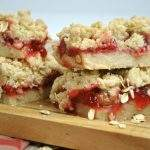 homemade cherry crumb bars stacked on a wooden cutting board