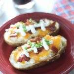 Baked Potato skins with bacon, cheese, sour cream and chives on a red plate