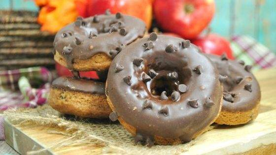 Apple Pumpkin Spiced Chocolate Chip Donuts in a stack in front of apples.
