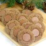 Soft chocolate gingerbread thumbprint cookies on a cutting board with greenery and pine cones.