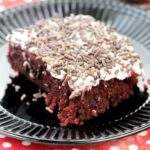 Red Velvet Poke Cake cut into a square, served on a black plate on a red and white polka dot napkin.