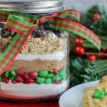A festive ribbon is tied around a jar of M&M Oatmeal Cookies in a Jar next to some holiday greenery and a plate of cookies.